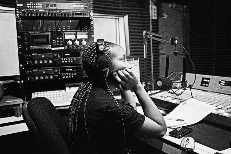 A woman at a mic in a radio studio.