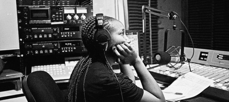 A woman sits at a mixing board in a radio station.