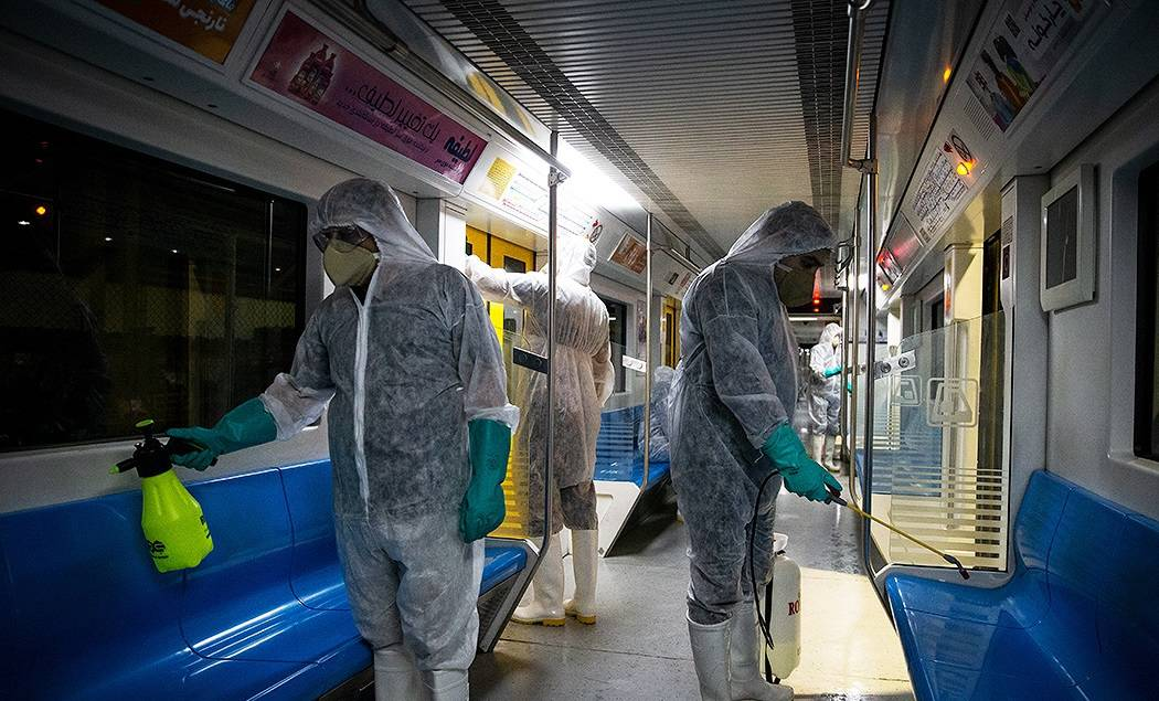 Three people in PPE disinfect the inside of a bus