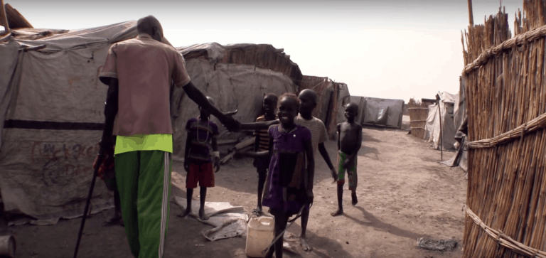 A man using a cane greets a group of children in a refugee camp.