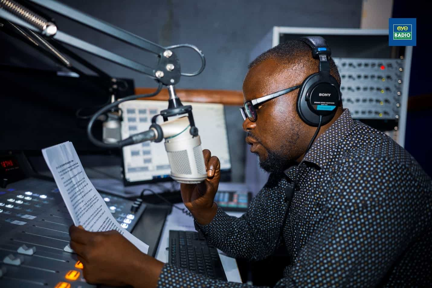 A man sits in front of a mic in a radio studio reading from a piece of paper