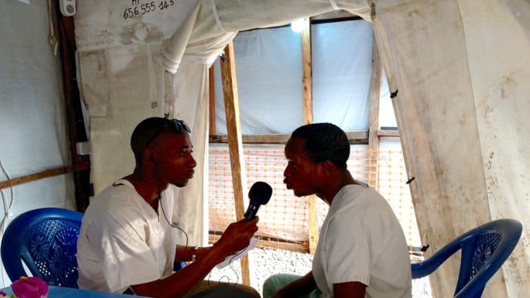 A man interviews another man in a tent.