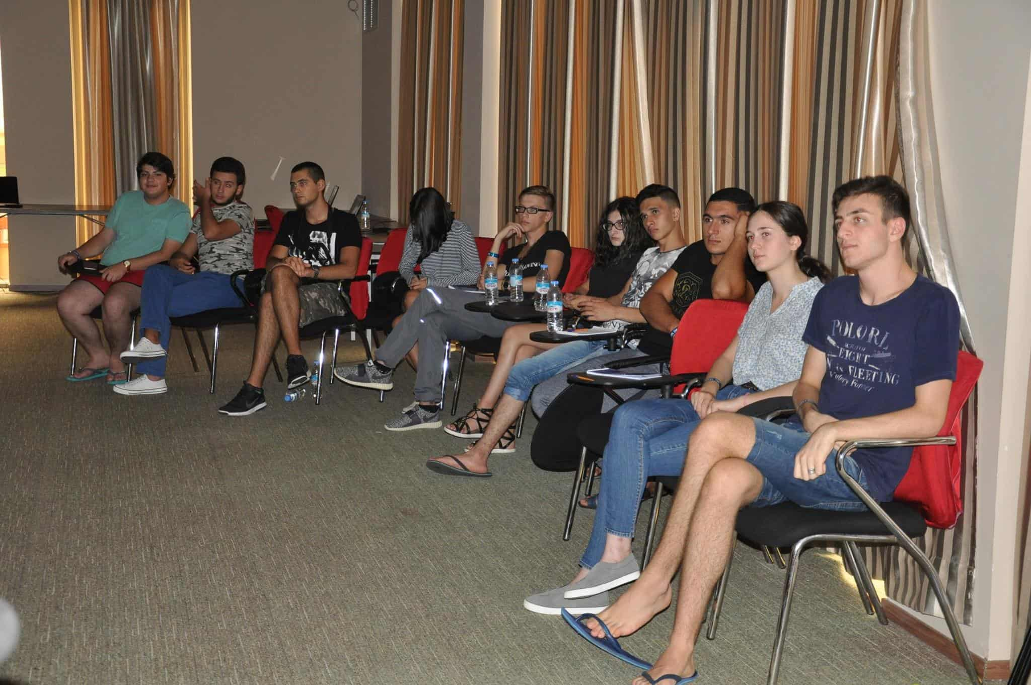 A group of young people sits in chairs in a room.