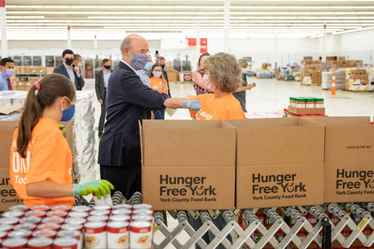 An older man bumps elbows with a woman standing by boxes of food.