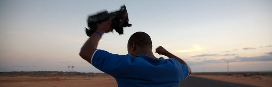 A man holds a video camera over his head.