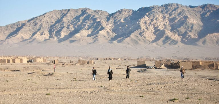 Treeless landscape with mountains in the background and three people standing near a small brick building.