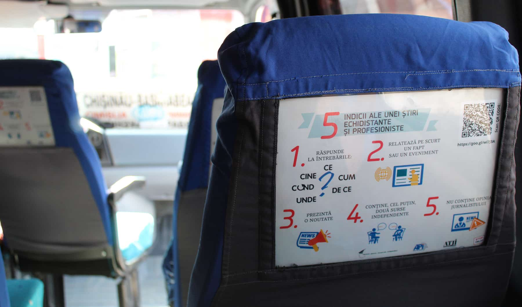 A poster is applied to the back of a seat in a mini bus
