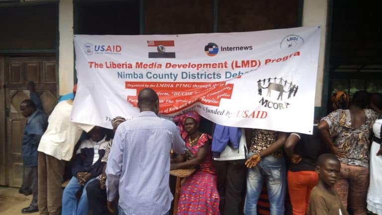 A group of people around a banner that says: The Liberia Media Development Program.