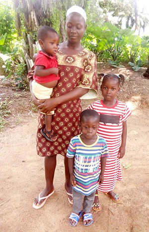 Woman stands holding a baby with 2 children by her site