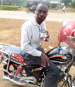 A man sits on a motorbike wearing a face mask and holding a card