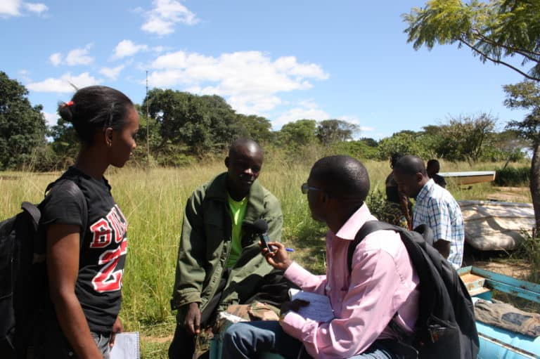 Three men sit outside by a grassy field interviewing while a woman watches.