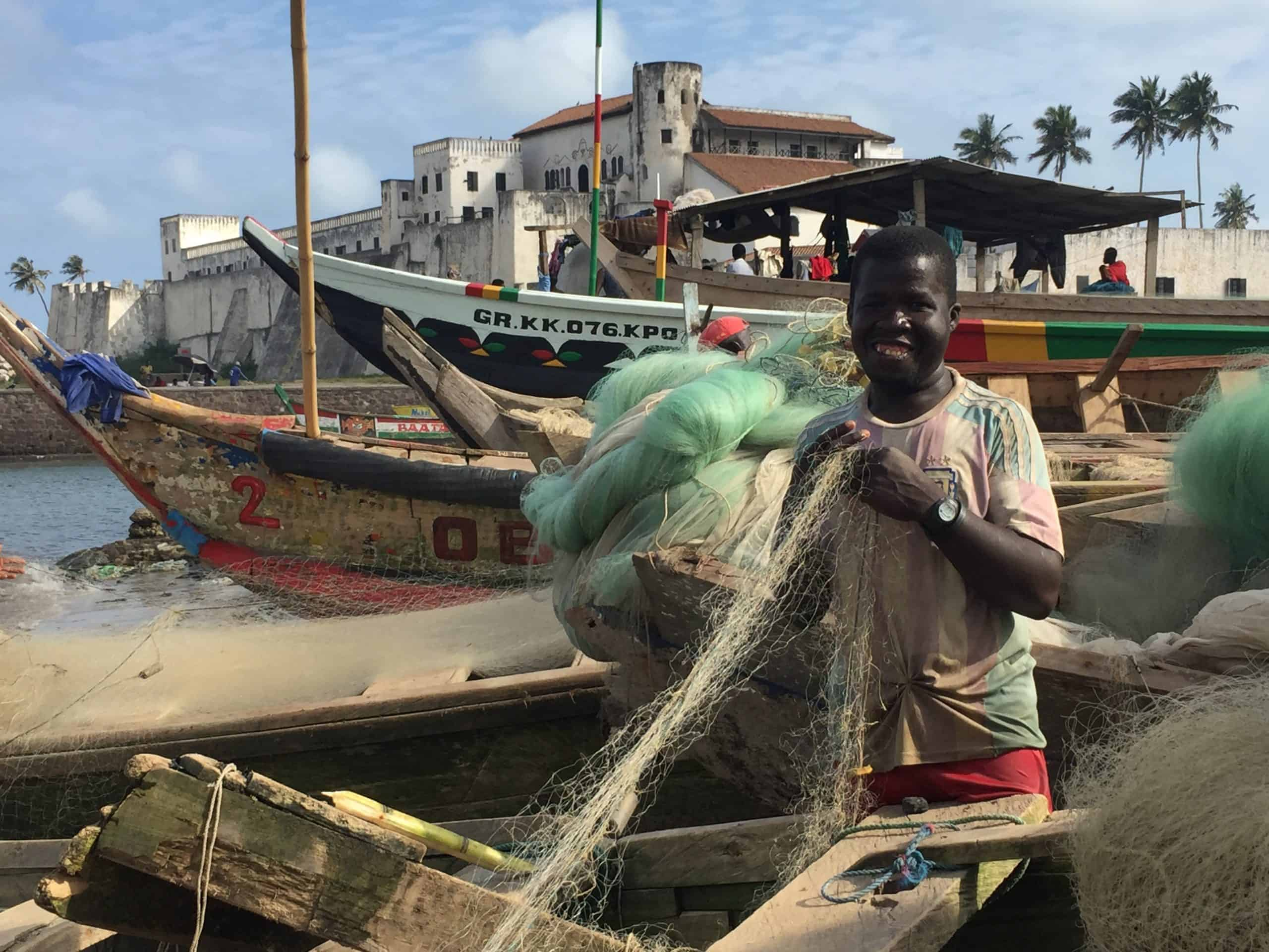 A man holds a fishing net by a boat.