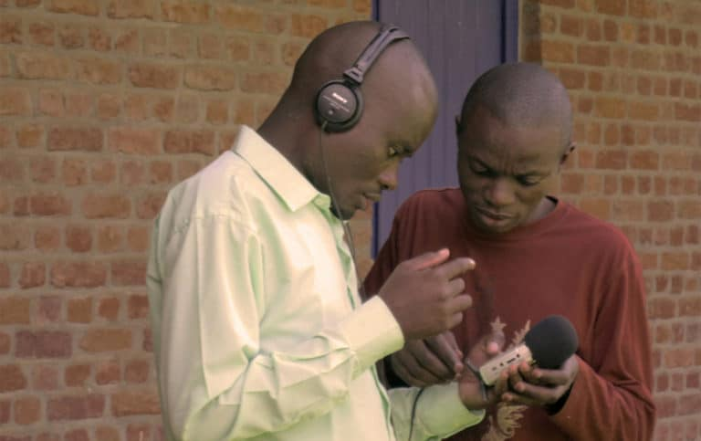 Two men look at an audio recorder.