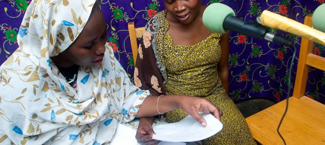 Two women sit by a mic in a radio studio.