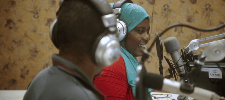 Two people sit in a radio studio