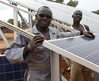 Two men stand by a solar panel installation