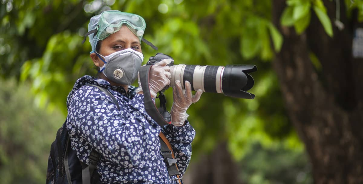 A woman wearing goggles, a face mask, and gloves holds a large camera