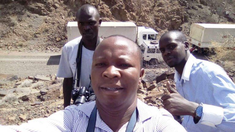 Three men take photos outside.