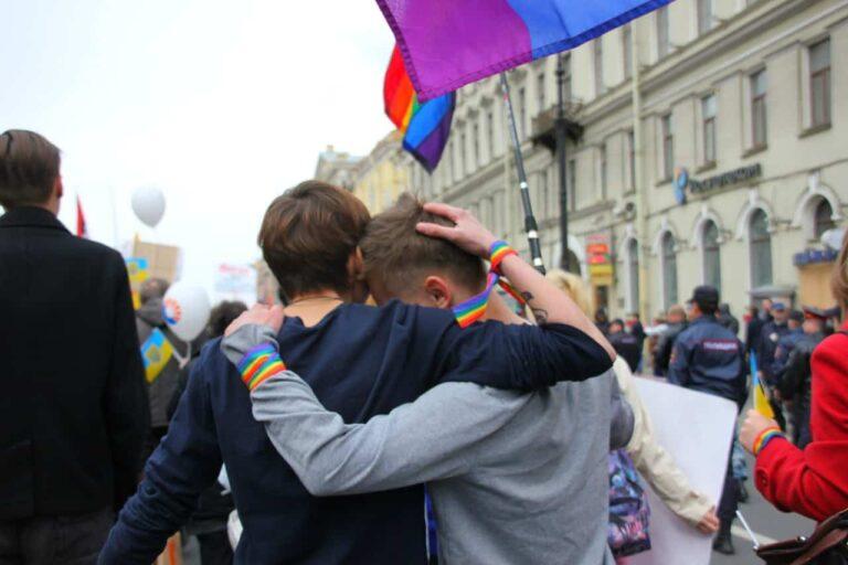 Two men hug at a gay pride parade.