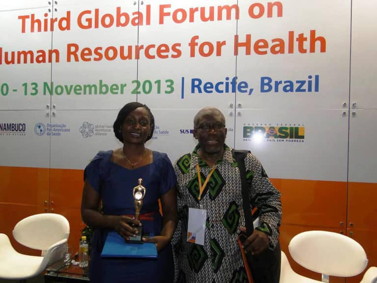 Two people seated on a stage with a banner behind them: Third Global Forum on Human Resources for Health.