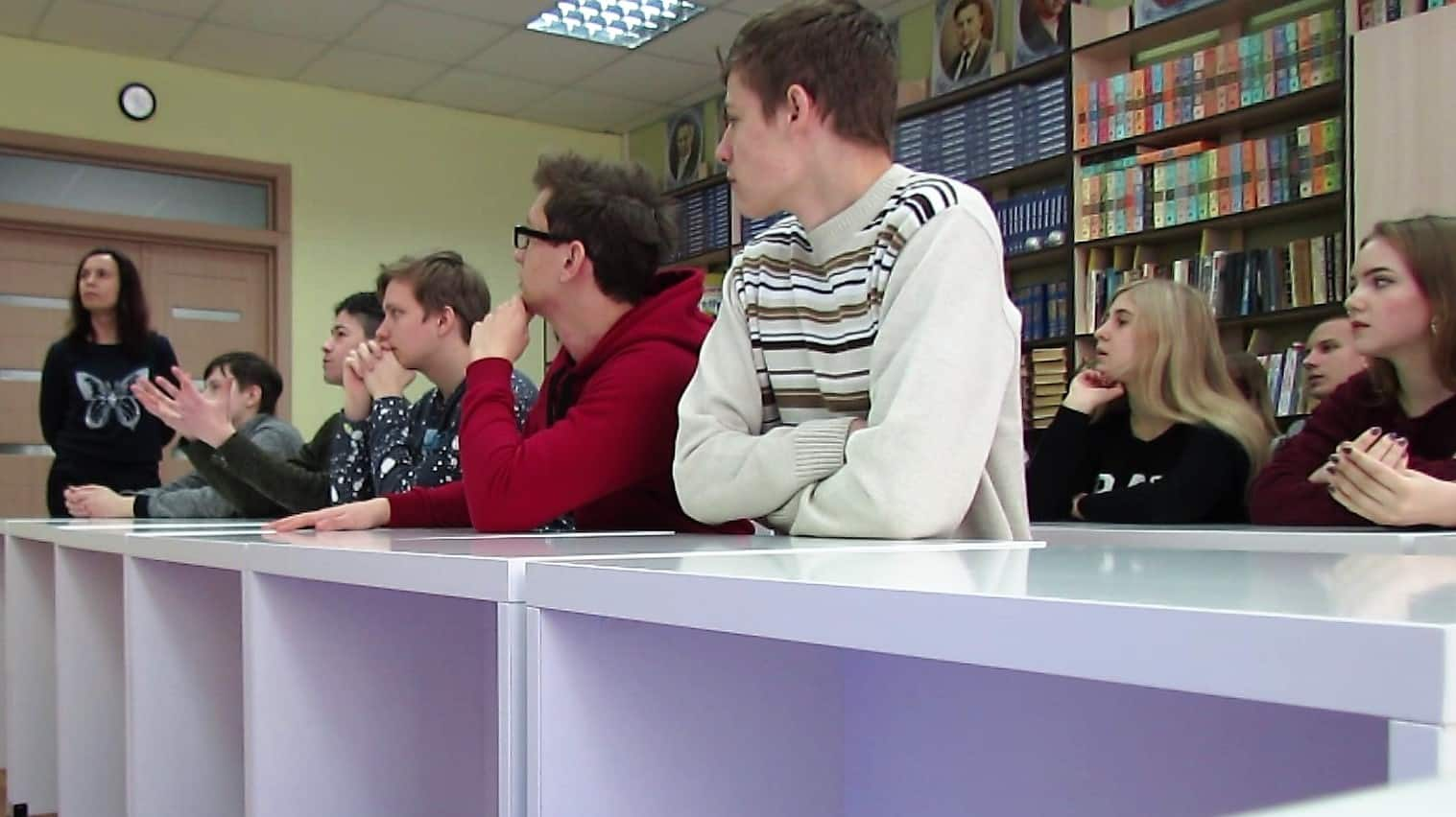 Students sit at white desks in a classroom, bookshelves are in the background
