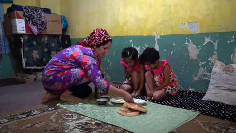 A woman puts plates of food in front of two girls who are sitting on a rug.