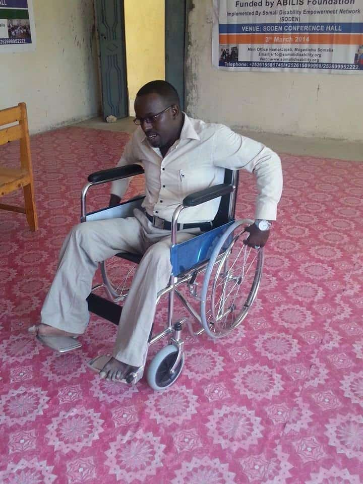 Mohamed pushes himself in his wheelchair across a room