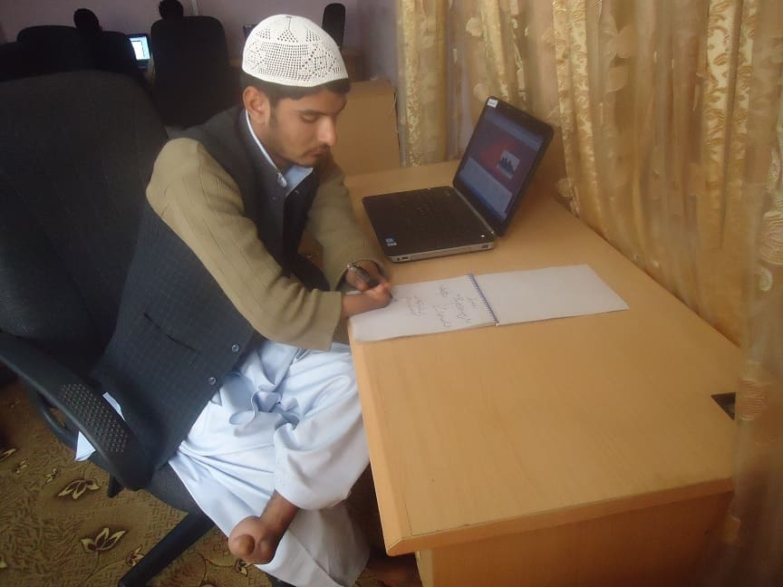 A man with a hand disability sits at a desk writing