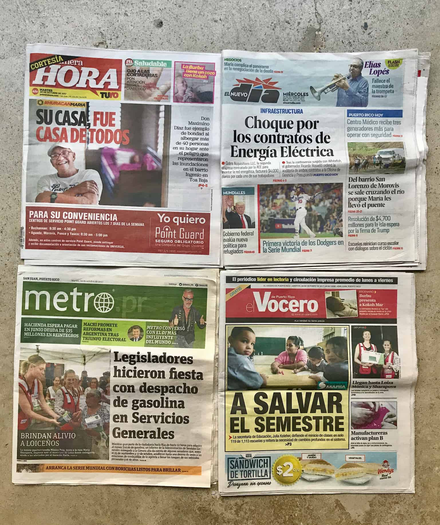 The front pages of 4 newspapers are tacked on a wall