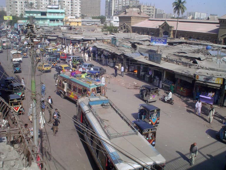 Buses and small cars on a crowded street.