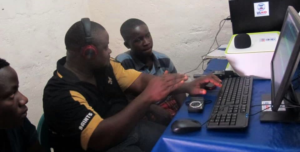 A man wearing headphones sits at a computer; there are two young men sitting on either side.