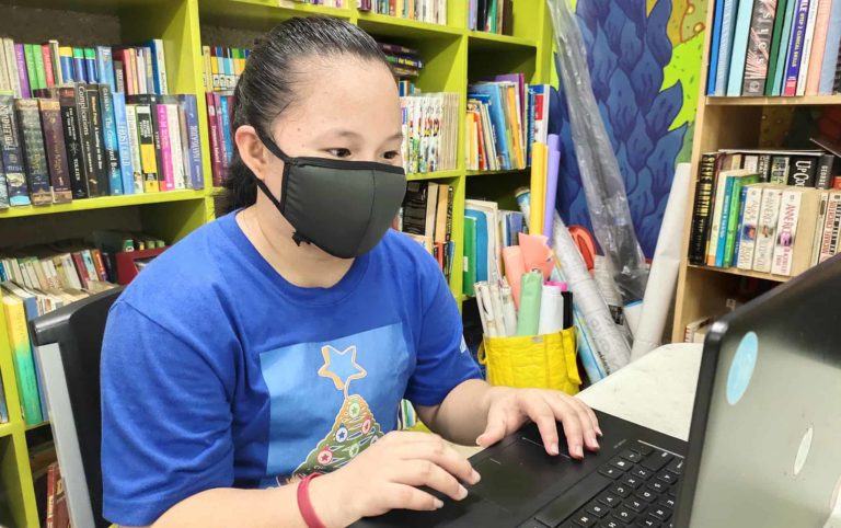 A young woman wearing a face mask sits typing at a computer