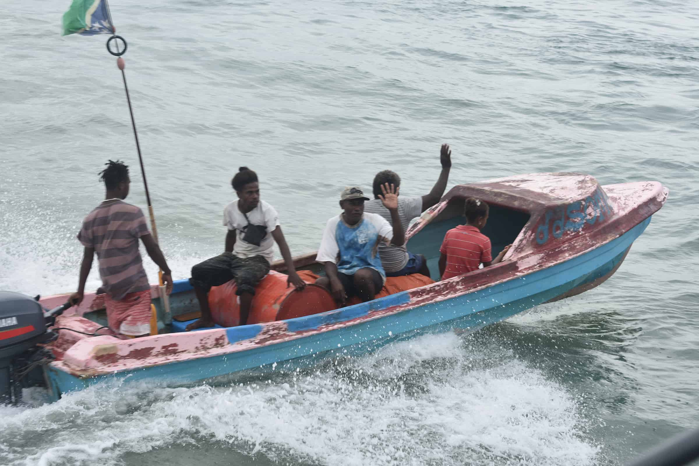 A group of people ride in a boat on a river