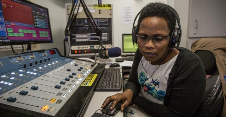 A woman wearing headphones sits in front of a mixing board in a radio studio