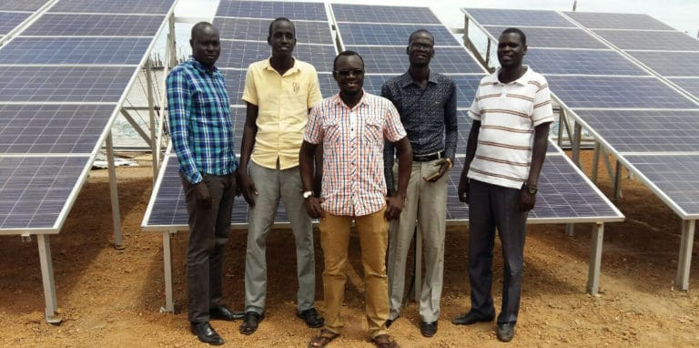 Five men stand in front of a bank of solar panels.