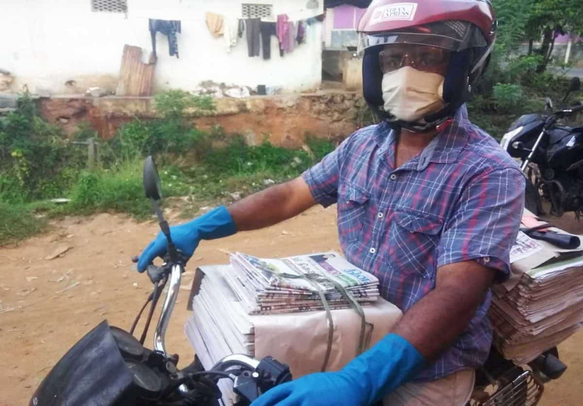 A man wearing a helmet, face mask, and rubber gloves sits on a motor bike loaded with newspapers.