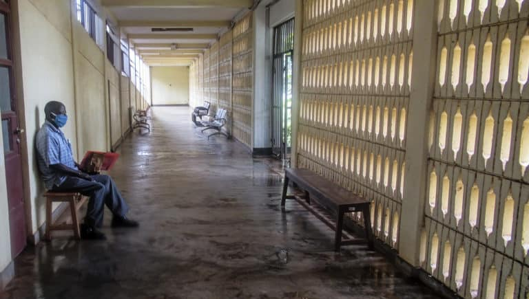 A man sits by himself in an empty hospital corridor.