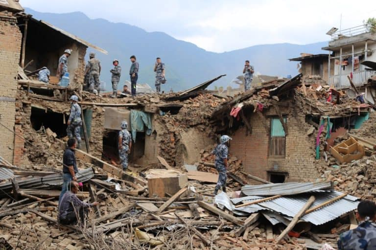 People in military gear look through the rubble of an earthquake-damaged building.