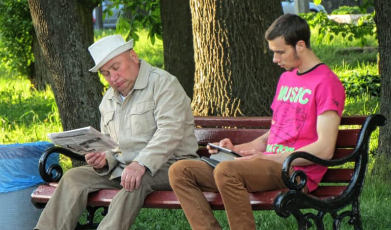 Two men sit on a bench; the older man reads a newspaper; the young man reads an tablet.