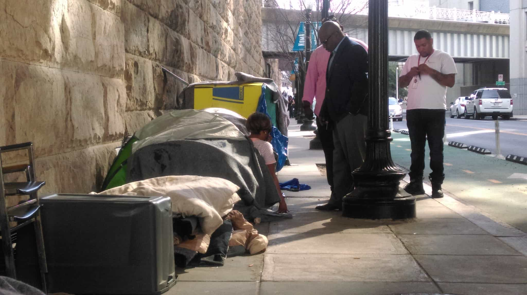 Three men stand by a line of tents pitched on a sidewalk in Washington, DC.