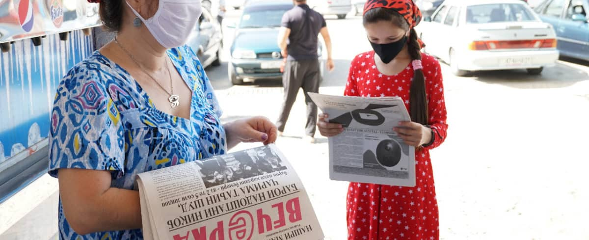 Two women wearing face masks stand in the street holding newspapers