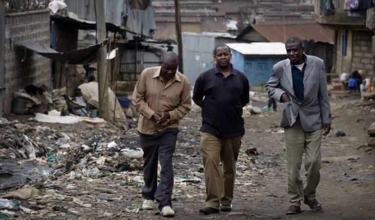 Three men walk down a garbage strewn dirt road.