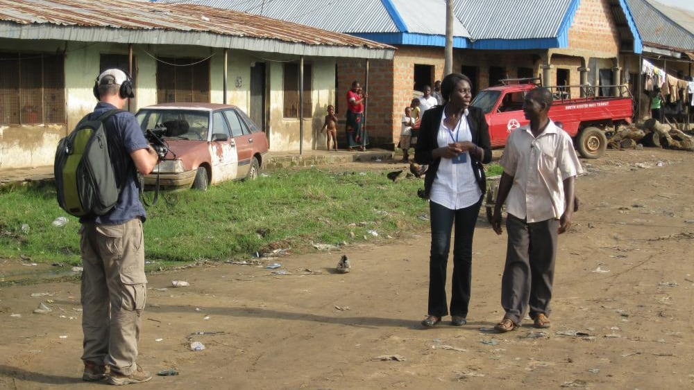 Ameto and a man walk down a dirt road while another man videotapes them