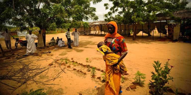 A woman holding a child in her arms walks through a dirt yard.
