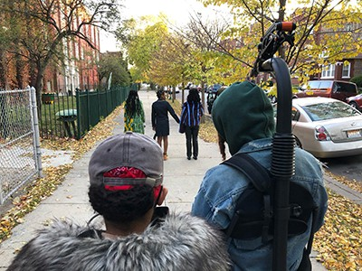 The backs of two people in the foreground who are filming 3 girls in the background