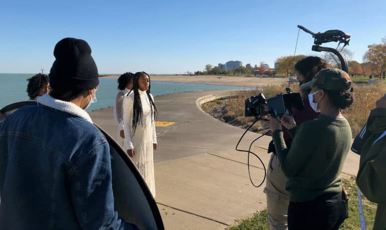Three young women with braided and curly hair wearing white dresses are filmed by a lake.
