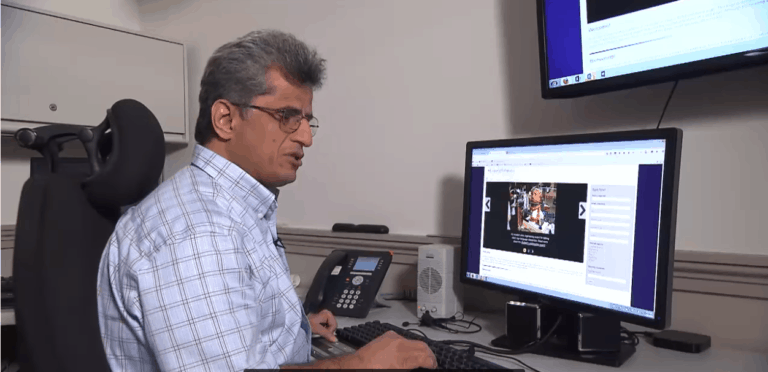 A blind man listens to the screen reader on his computer.