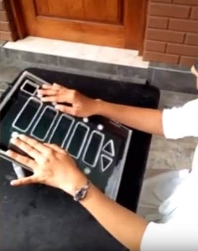 Two hands are shown on a device used for voting
