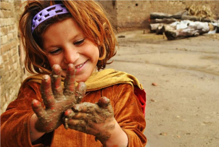 A little girl smears mud on her hands.