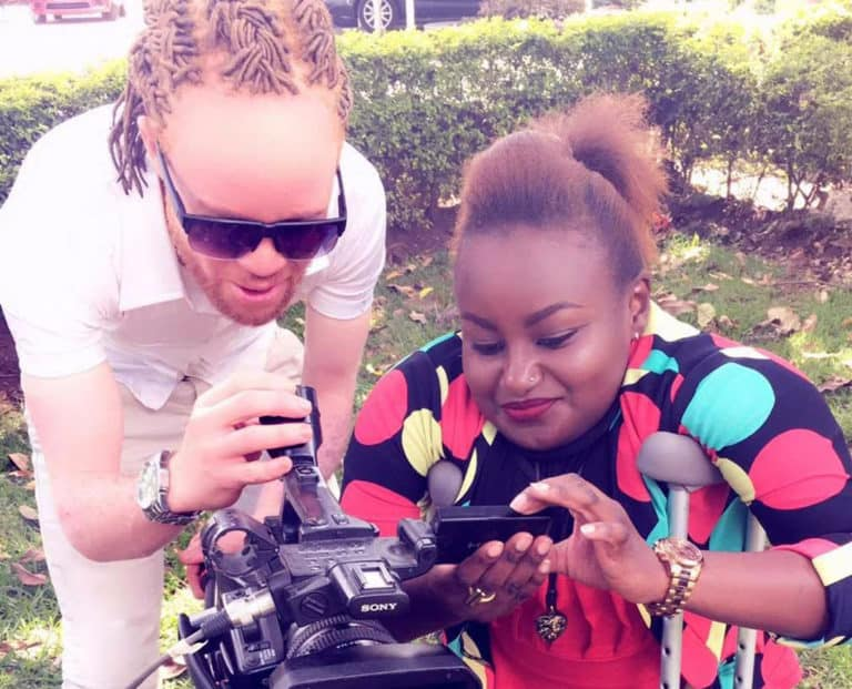 A light skinned man with braided hair and a dark skinned woman on crutches look at a video camera